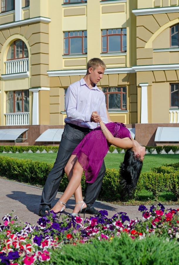 Danse de salle de bal de couples dans un jardin photo stock
