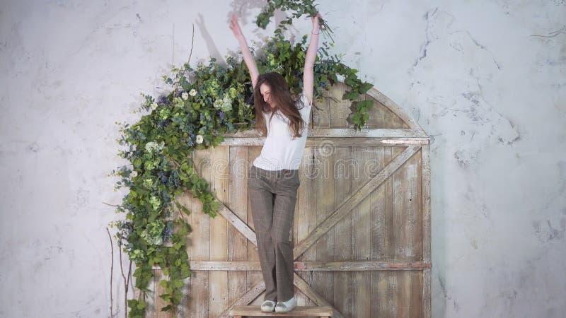 Danse de sourire heureuse de fille sur un escabeau sur le fond d'une belle porte en bois décorée des fleurs images libres de droits