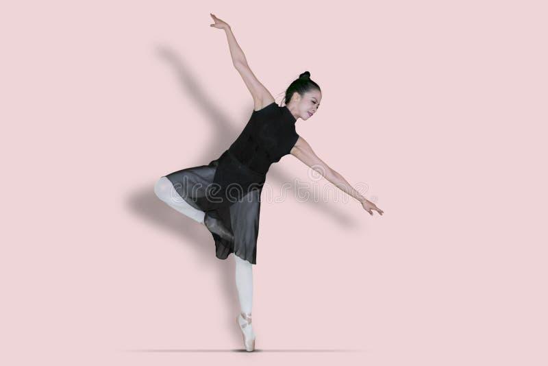 Danse femelle de ballerine avec des poses de pointe du pied dans le studio image libre de droits