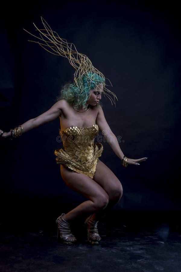 Danse, femme latine avec les cheveux verts et costume d'or avec le handm image libre de droits