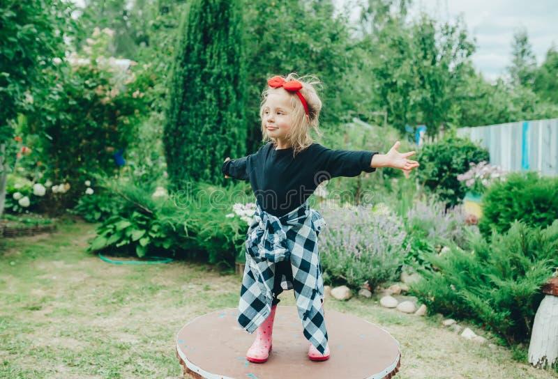 Danse gaie artistique de petite fille dans le jardin d'arrière-cour dans le village image libre de droits