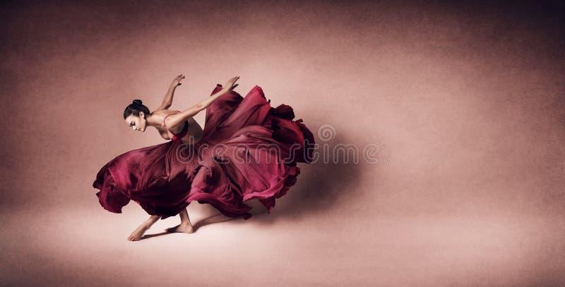 Danse gracieuse de femme dans la robe rouge foncé débordante images stock