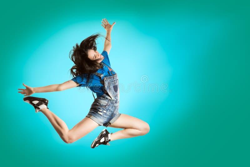 Danse heureuse de fille de style moderne sur le fond bleu frais Concept sautant de danseur de Hip Hop photos libres de droits