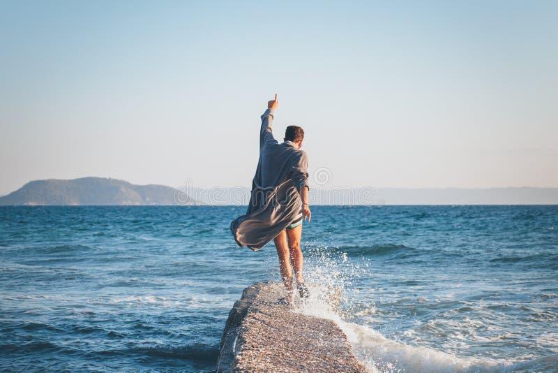 Danse heureuse de jeune homme sur le dock image stock