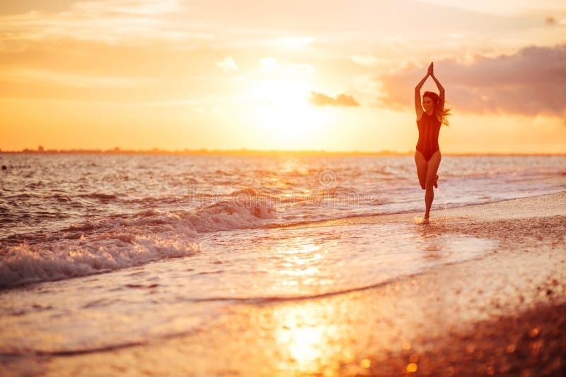 Danse insousiante de femme dans le coucher du soleil sur la plage photo libre de droits