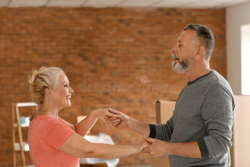 Danse mûre heureuse de couples à l'intérieur Entr?e dans la nouvelle maison images stock