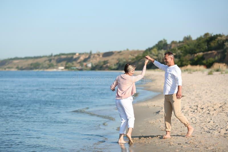 Danse mûre heureuse de couples à la plage photo stock