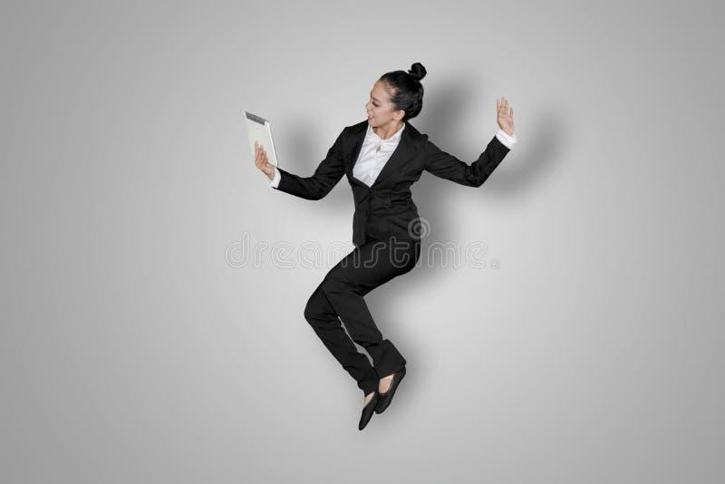 Danse réussie de femme d'affaires avec un comprimé images stock