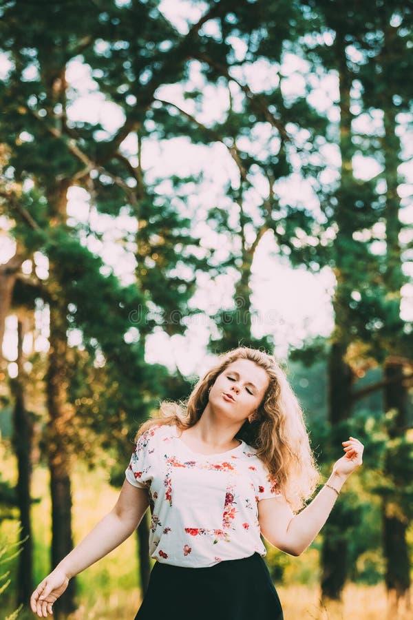 Danse riante de sourire heureuse caucasienne de femme de fille de jeune jolie taille de plus en été Forest Fun Enjoy Outdoor vert image libre de droits