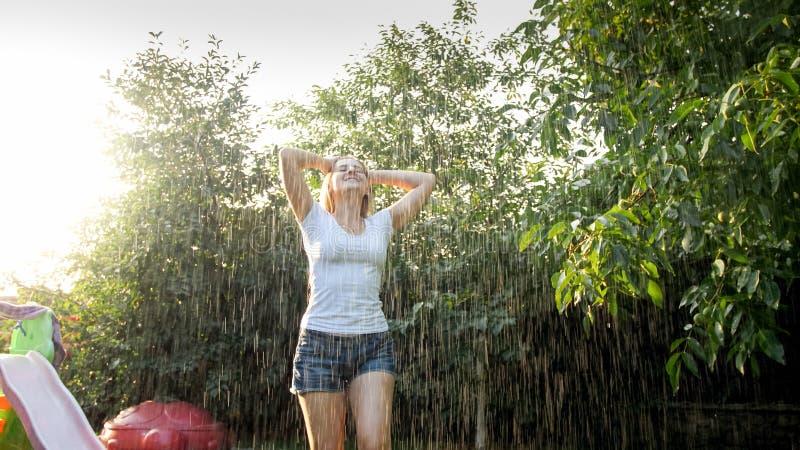 Danse riante heureuse de jeune femme sous la pluie au jardin Fille jouant et ayant l'amusement dehors ? l'?t? image stock