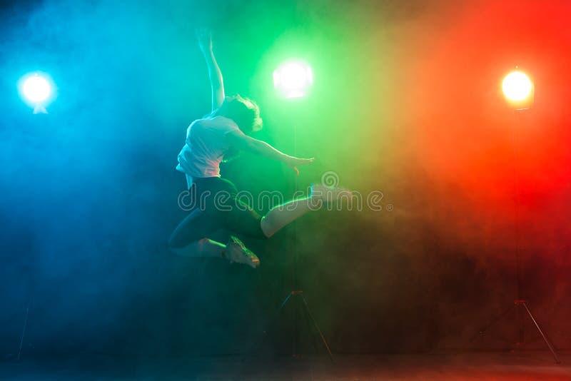 Danse, sport, trouille de jazz et concept de personnes - la jeune femme sautent dans l'obscurité sous la lumière colorée photos stock