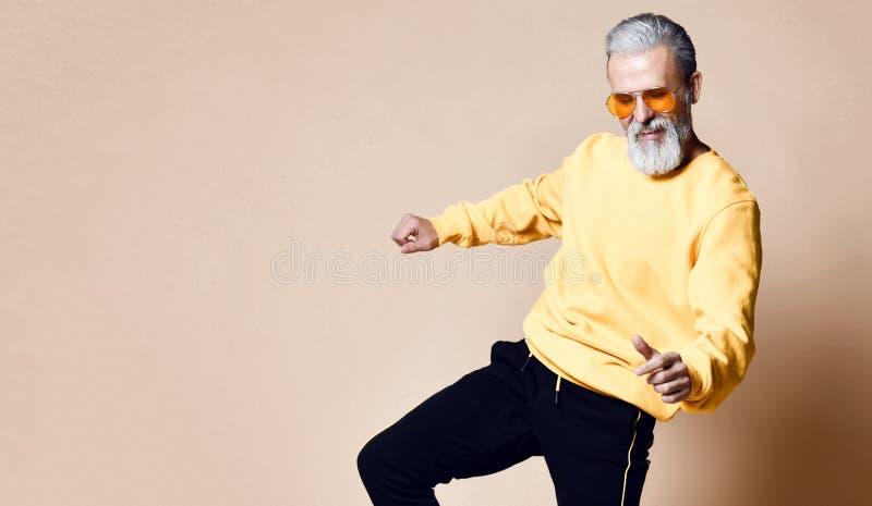 Danse supérieure heureuse d'homme de millionnaire chez les hommes à la mode élégants de lunettes de soleil jaunes supérieurs photographie stock libre de droits