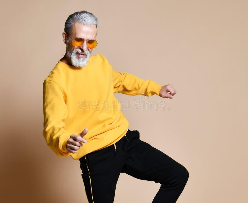 Danse supérieure heureuse d'homme de millionnaire chez les hommes à la mode élégants de lunettes de soleil jaunes supérieurs photo libre de droits