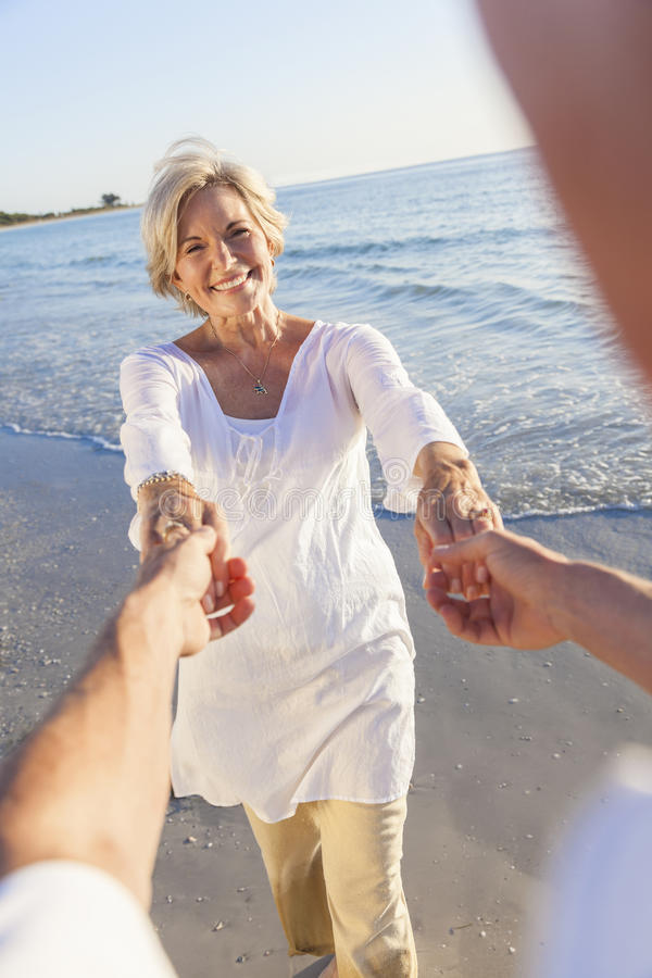 Danse supérieure heureuse de couples retenant des mains sur une plage tropicale photos stock