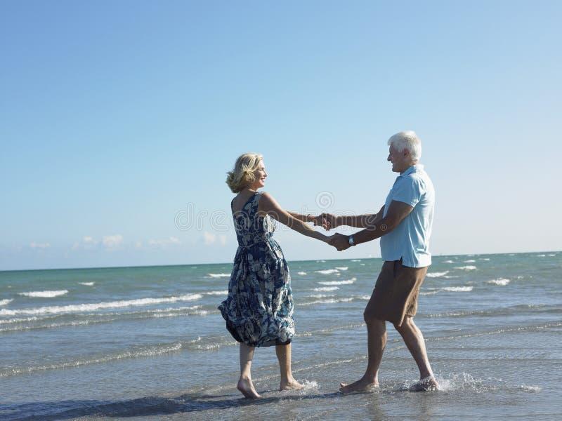Danse supérieure heureuse de couples sur la plage tropicale photo stock