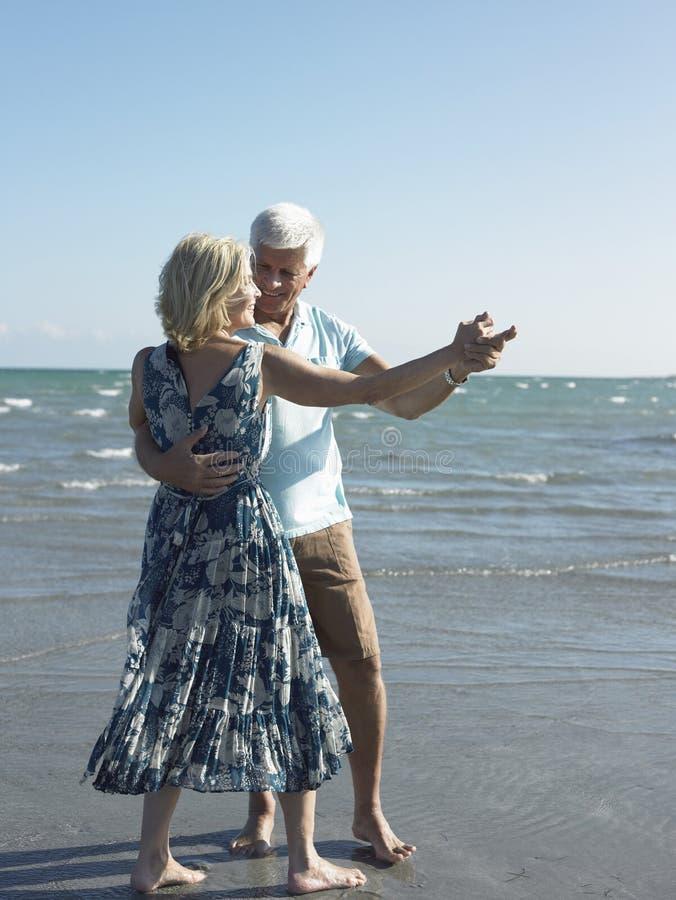 Danse supérieure heureuse de couples sur la plage tropicale photographie stock
