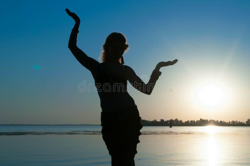 Danse tribale de danse de femme sur la plage à l'aube photos libres de droits