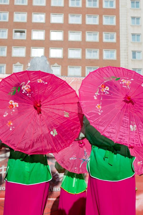 Dansen för traditionell kines, med rosa färgpappersparaplyer öppnar royaltyfria bilder