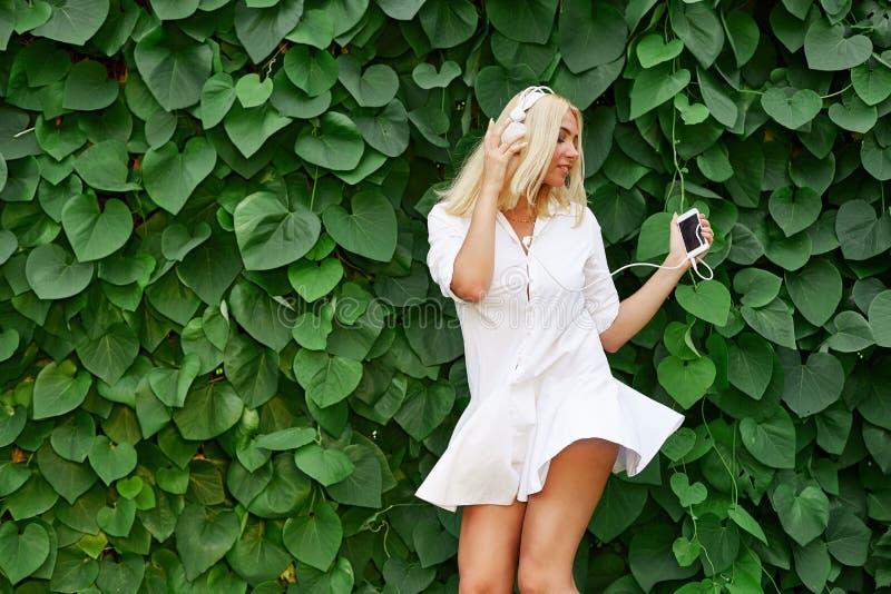 Dansend blondemeisje met het luisteren aan muziek op een smartphone royalty-vrije stock afbeeldingen