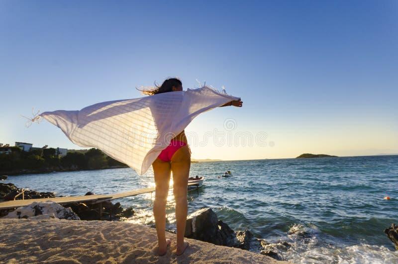 Dansend gelukkig meisje op de strandzonsondergang royalty-vrije stock afbeelding