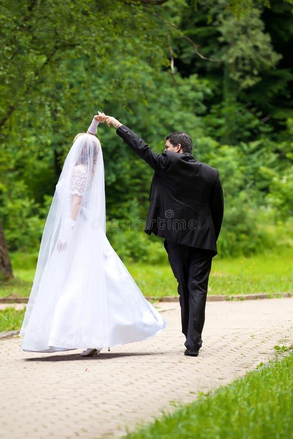 Dansend huwelijkspaar bij een park stock fotografie