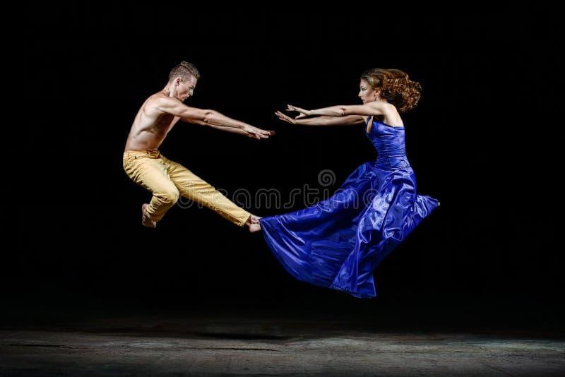 Dansend paar in de duisternis, sprong in de dansbeweging stock afbeelding