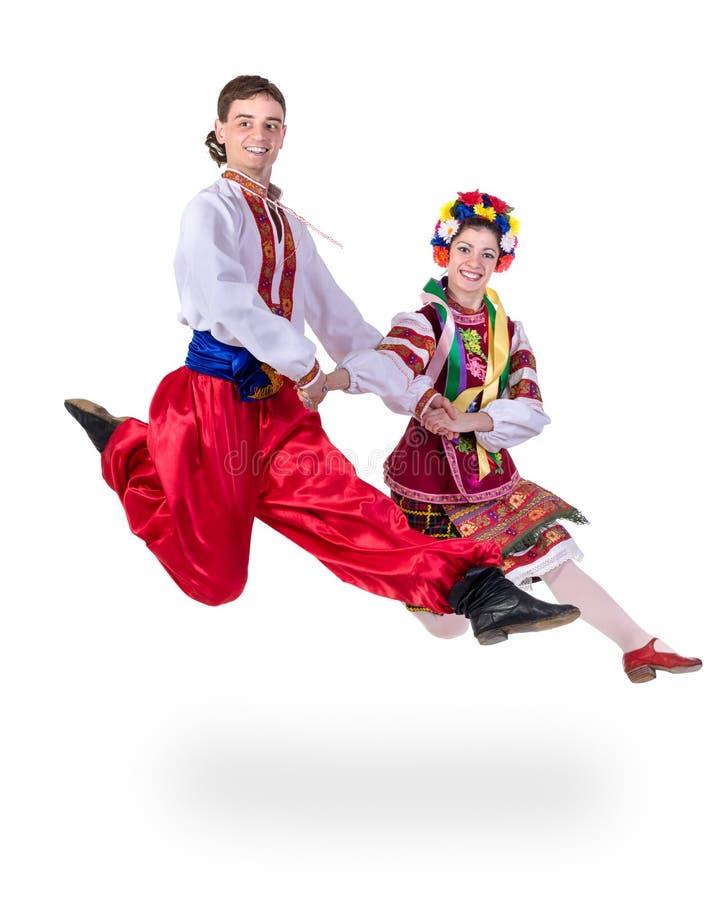 Dansend paar die in poetsmiddel nationaal traditioneel kostuum, volledig geïsoleerd lengteportret springen stock afbeelding