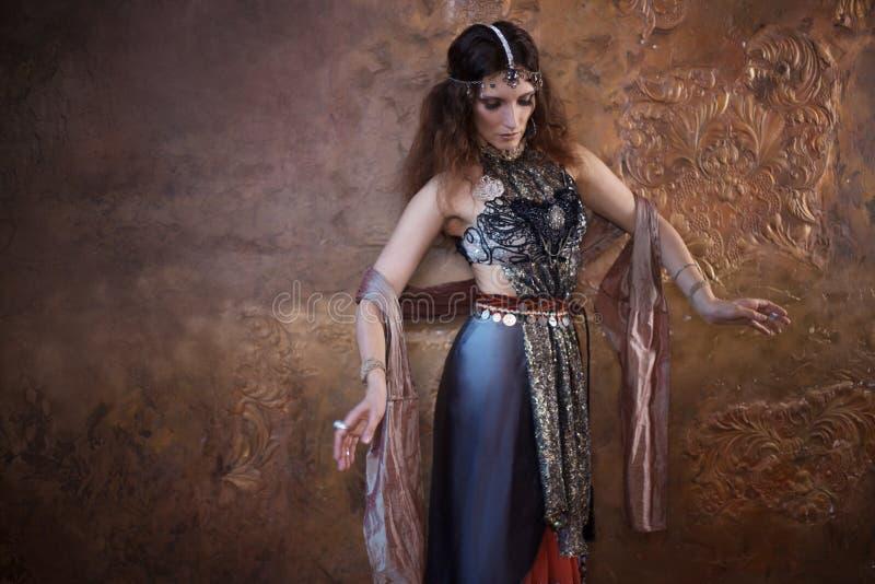 Dansende mooie vrouw in Indisch kostuum op een geweven achtergrond stock foto