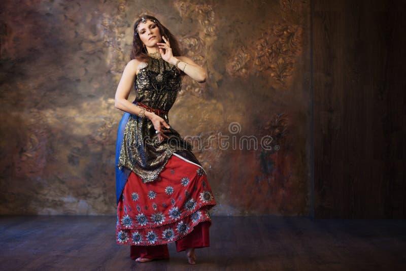 Dansende mooie vrouw in Indisch kostuum op een geweven achtergrond stock fotografie