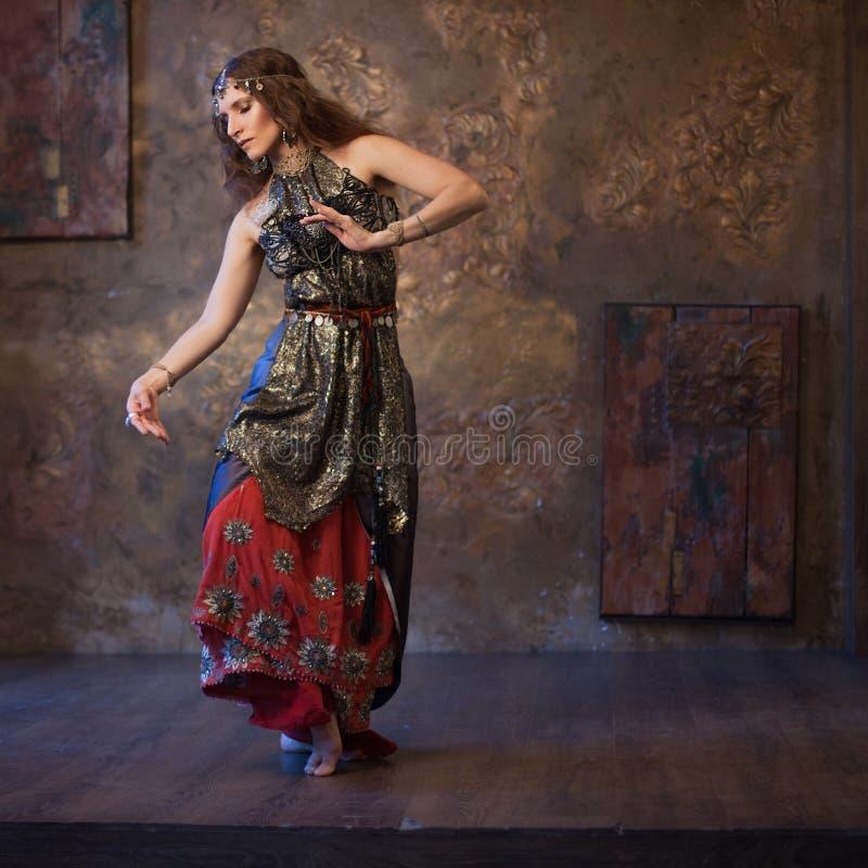 Dansende mooie vrouw in Indisch kostuum op een geweven achtergrond stock foto's