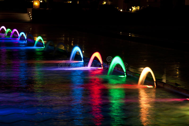 Dansende Multi Gekleurde fontein bij donkere nacht stock foto's