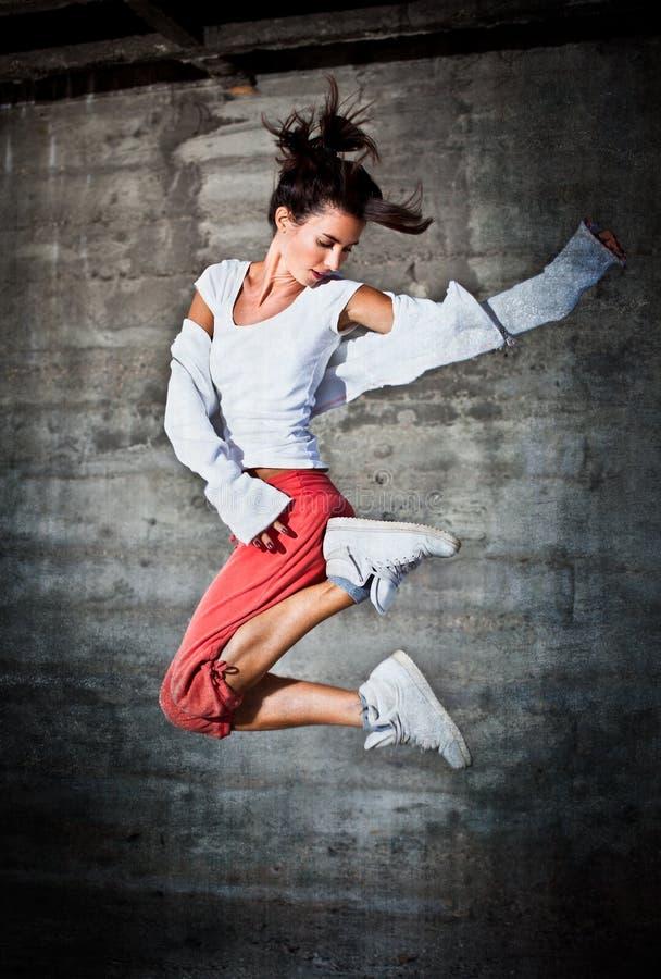 Dansende vrouw met gelukkige gelaatsuitdrukking die omhoog springt stock afbeelding
