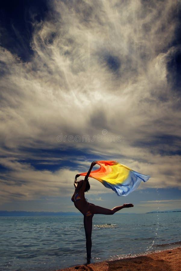 Danser bij het overzees tijdens zonsondergang royalty-vrije stock afbeelding