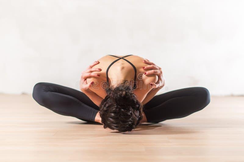 Danser die geavanceerde de oefeningszitting doen die van de vlinderrek voorwaartse holdingsschouders leunen Jonge flexibele vrouw stock foto