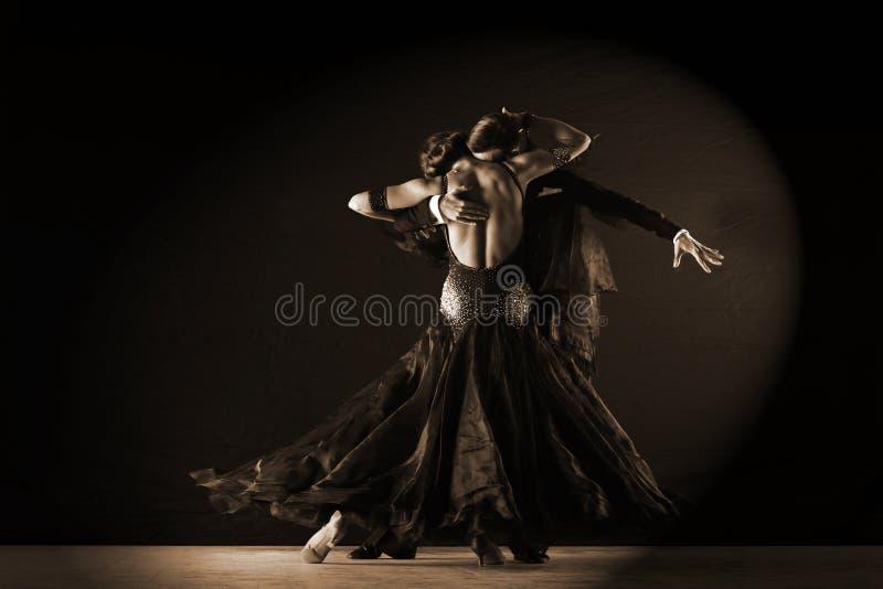 Dansers in balzaal tegen op zwarte achtergrond stock foto