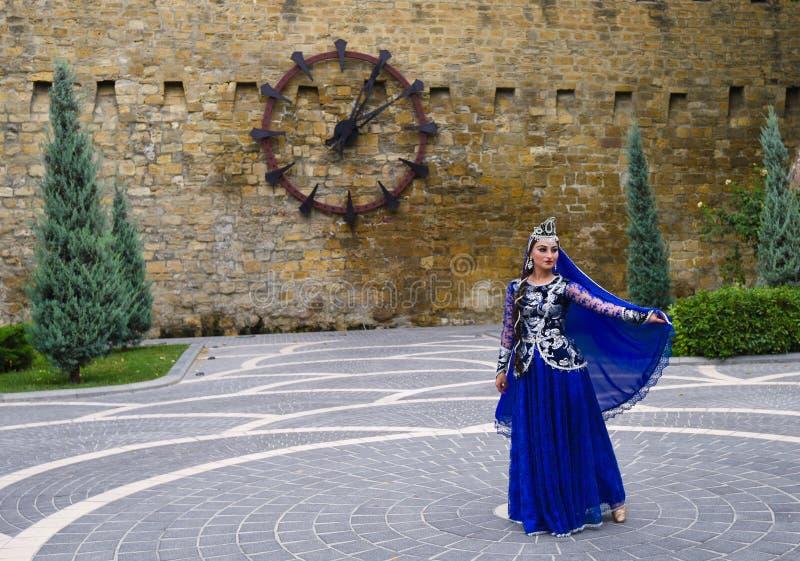 Dansersmeisje bij vestingwerk met klokken stock foto