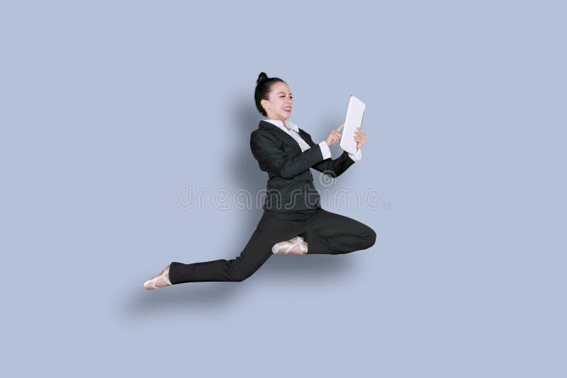 Danses asiatiques de femme d'affaires avec le comprimé sur le studio photographie stock
