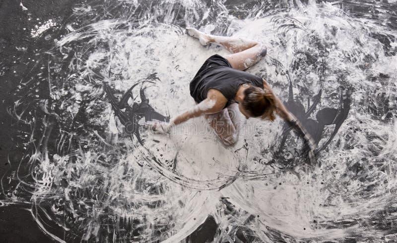 Danses de jeune femme sur le plancher d'une manière élégante décoratif, dans la couleur grise et blanche Art de corps expressif c photos libres de droits