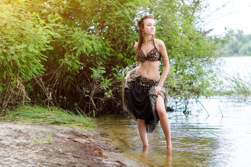 Danseur américain tribal de style de jeune femme Danse de fille et pose sur le costume de port de danse de ventre de sable de pla photo stock