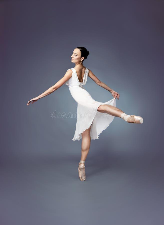 Danseur-ballerine de ballet sur des chaussures de point avec une robe blanche image libre de droits