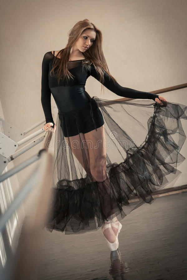 Danseur classique au barre de ballet sur une pointe du pied photographie stock libre de droits