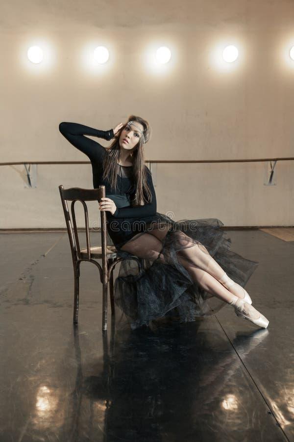 Danseur classique contemporain sur une chaise en bois sur une répétition photos stock