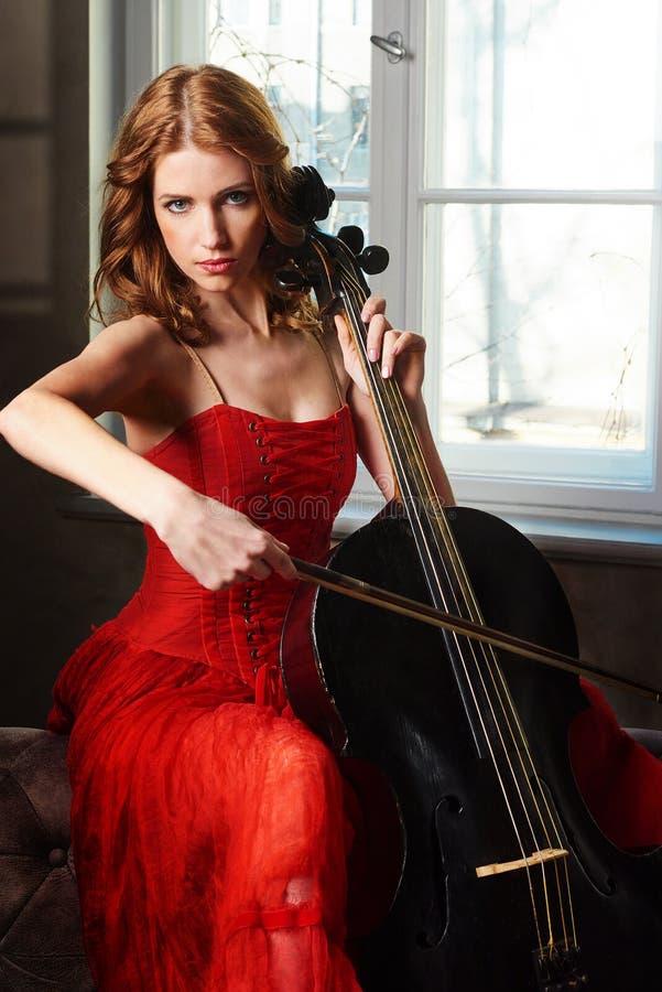 Danseur classique dans la robe rouge et pointe jouant sur le violoncelle noir antique photos stock