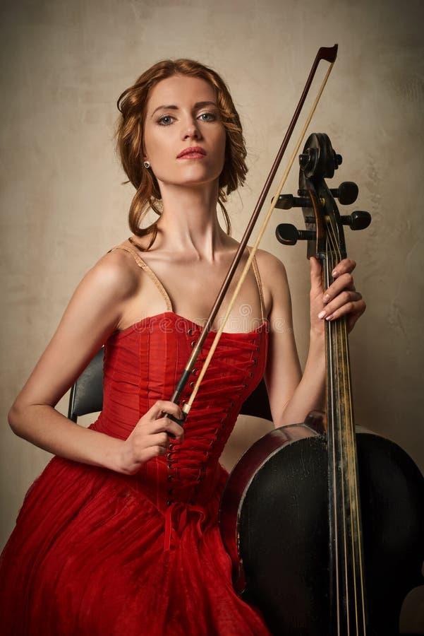Danseur classique dans la robe rouge et pointe jouant sur le violoncelle noir antique photo libre de droits