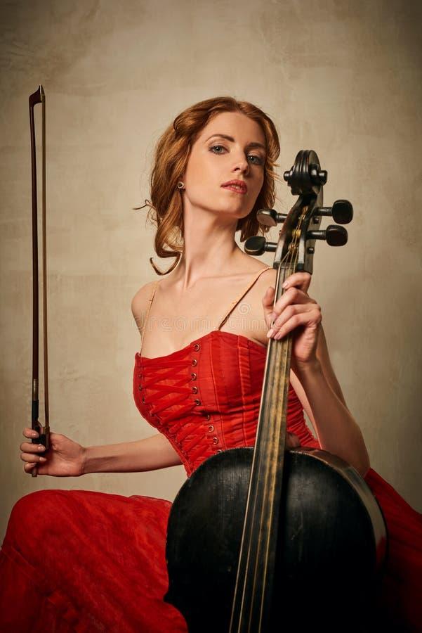 Danseur classique dans la robe rouge et pointe jouant sur le violoncelle noir antique image libre de droits