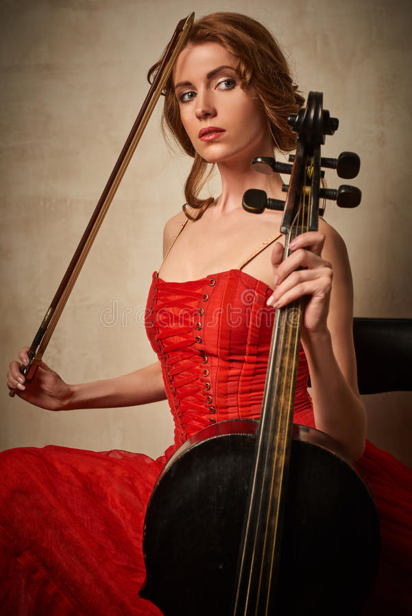 Danseur classique dans la robe rouge et pointe jouant sur le violoncelle noir antique images stock