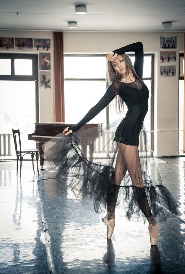 Danseur classique féminin posant sur un toptoe dans une classe de danse photo libre de droits