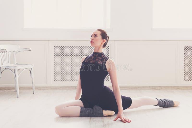 Danseur classique classique s'étirant dans le cours de formation blanc photos stock