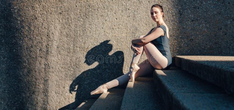 Danseur classique s'asseyant sur des escaliers portant des chaussures de pointe images stock