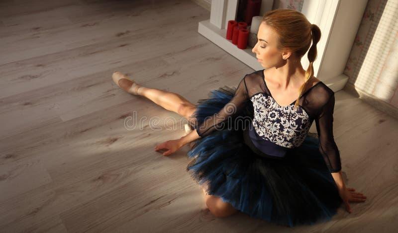 Danseur classique s'asseyant sur le plancher en bois Ballerine féminine ayant un concept de ballet de repos images libres de droits